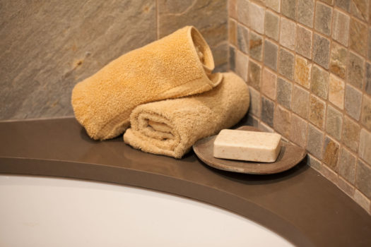 Two rolled towels with soap dish on rim of tub set against stone wall tiles.