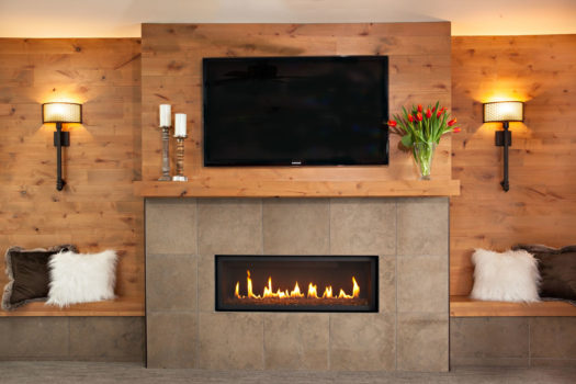 Half knotty pine half slate tile covered fire place with matching bench seating on both sides