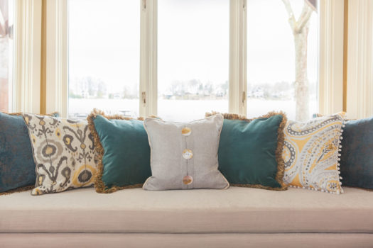Cream colored cushioned long bench with multi colored pillows in front of window overlooking lake