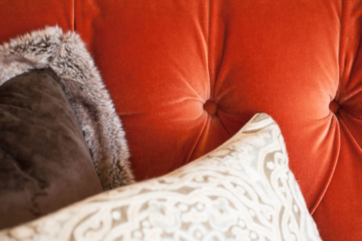 Orange buttoned seating back with various textured throw pillows