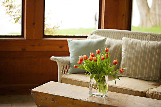 Wicker seating with rustic wood coffee table and vase of red tulips.