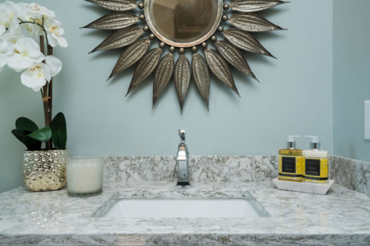 Stone sink with light bronzed sunflower shaped wall mirror in bathroom with bright yellow accent soaps and white orchid in silver hammered vase.