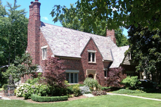 Front of two story brick Tudor home.