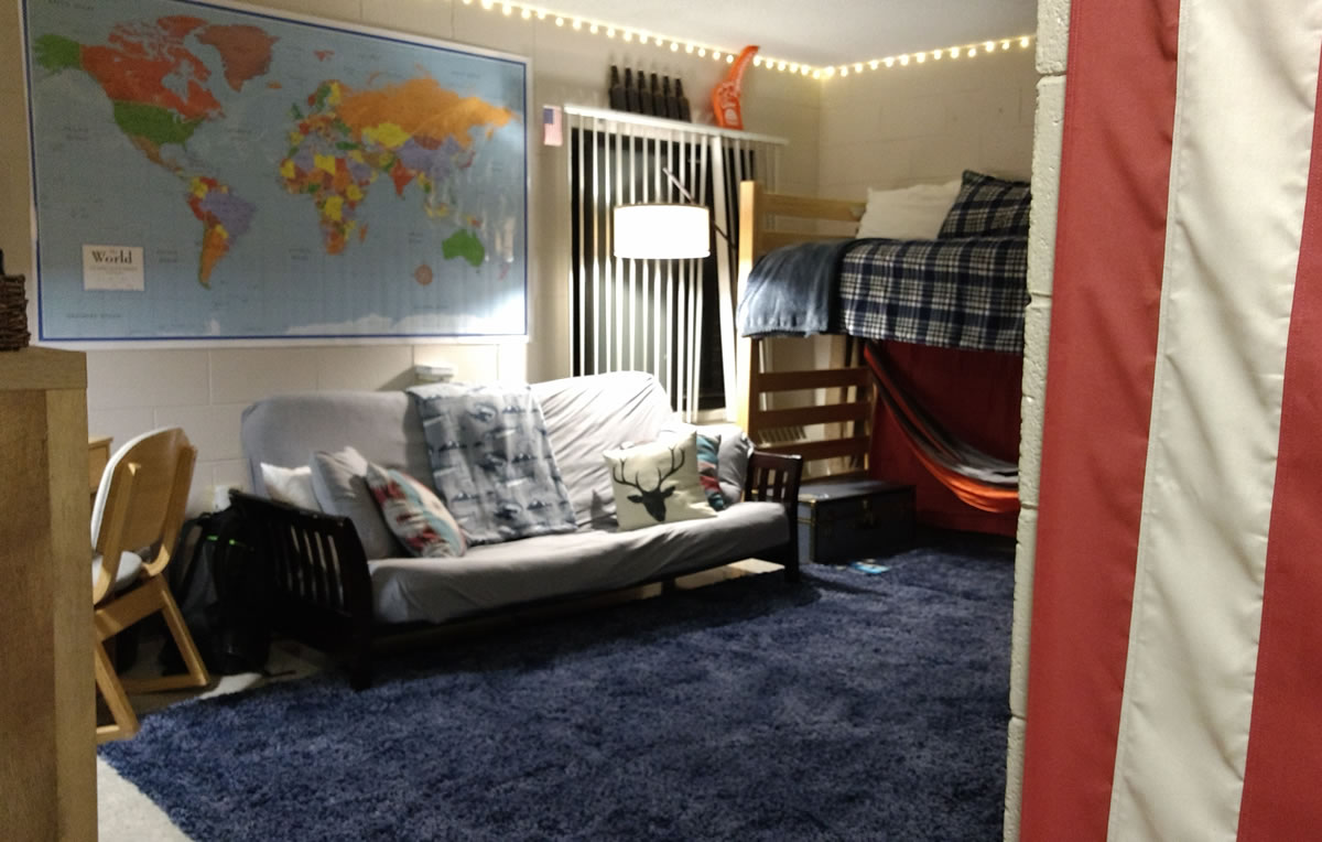 College Dorm with large flat map on wall above white futon next to raised bed.