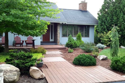 View of ranch home with wooden plank walkway leading to front door and chaired patio