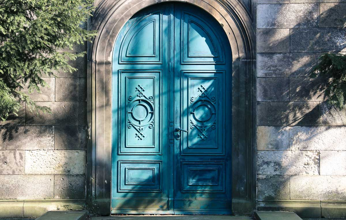 Stone building with curved archway with curved blue painted wooden door.