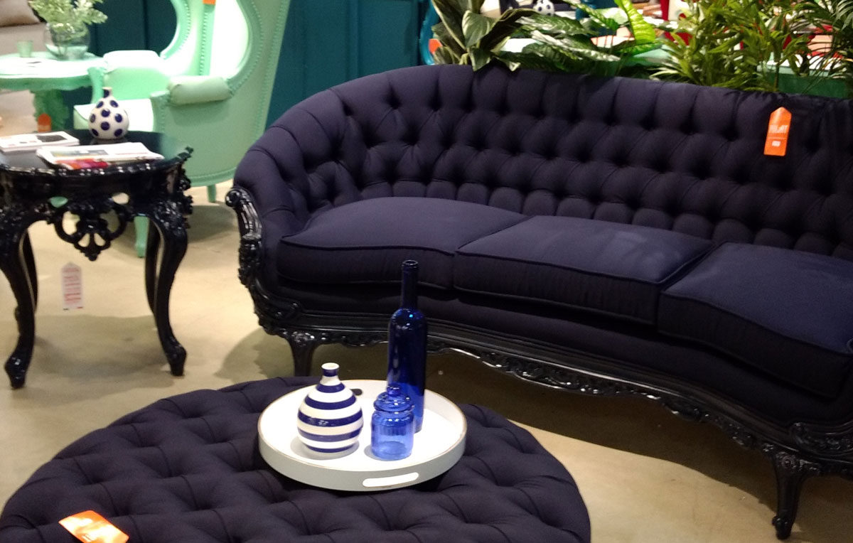 Royal blue Victorian sofa and round tufted ottoman/table.