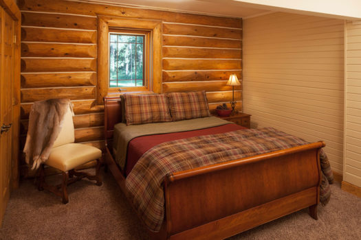 Sleigh-bed with half pine paneled walls and small window