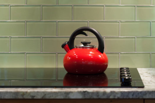 Red tea kettle on glass stove top against apple green glass subway tiles.