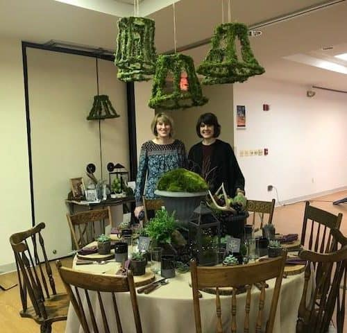 two women standing in front of a decorated dining room table