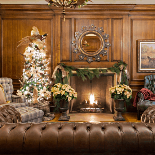 Lit fireplace in the middle of a room with leather sofas and armchairs at Christmas time